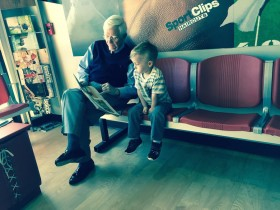 Owen reading with a man at Sport Clips