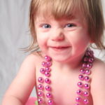 expressive toddler wearing beads