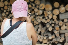 woman photographing wood pile