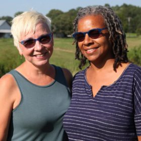 Interracial female couple smiling while standing next to each other outside in the country