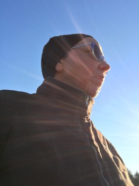 Woman wearing winter cap and coat in a ray of sunlight