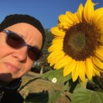 Woman wearing winter hat and sunglasses standing next to a sunflower.