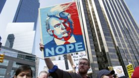protestor holding sign with illustration of Trump and word NOPE